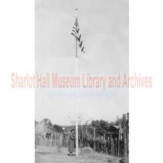 Sharlot Hall standing at flagpole at Sharlot Hall Museum