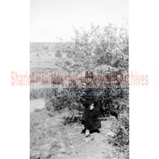 Sharlot Hall in hat standing before large bush