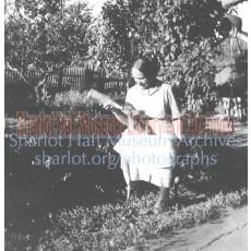 Sharlot Hall bottle-feeding piglet in her lap