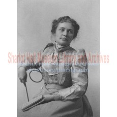 Sharlot seated and holding book