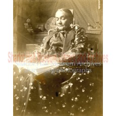 Adeline Hall seated with book in lap