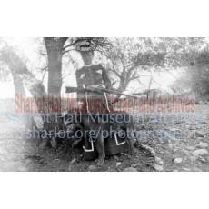 Sharlot Hall holding rifle standing before dog